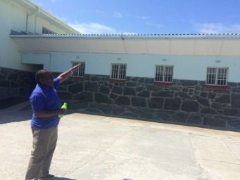 Tour Guide/Former Political Prisoner at Robben Island pointing to Nelson Mandela's cell on the far right